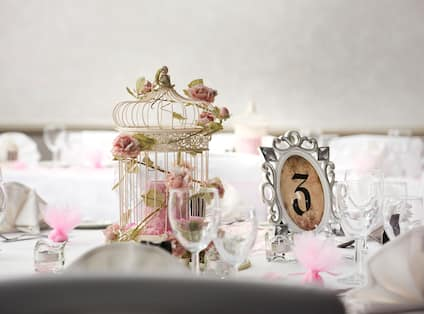 Place Settings, Wine Glasses, Framed Table Number, Bird Cage, and Wedding Favors on Round Tables With White Linens Decorated for Wedding Reception