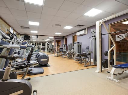 Cardio Equipment, Mirrored Wall, Entry, and Weight Bench in LivingWell Fitness Room