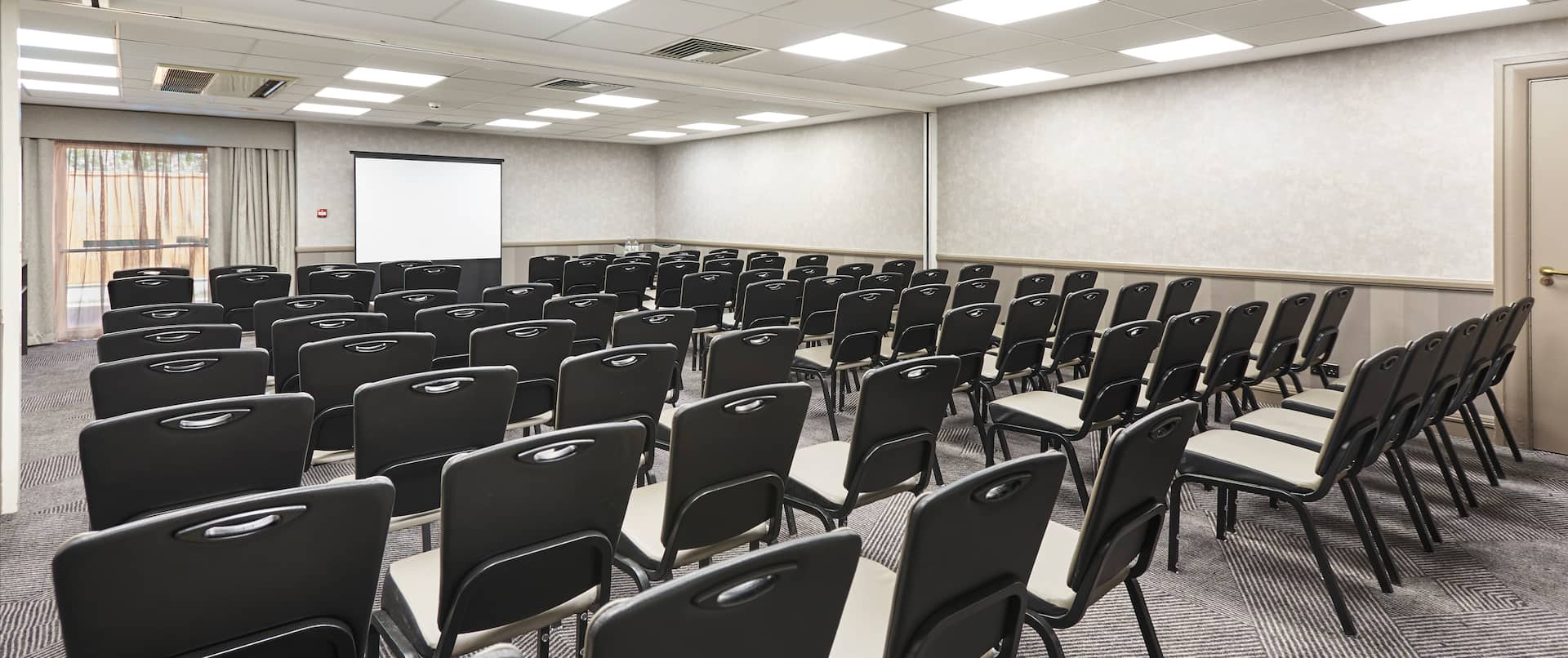Enbourne Suite Arranged Theater Style With Rows of Chairs Facing Projector Screen and Window With Sheer Drapes