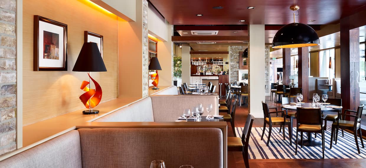 Wall Art, Tables With Place Settings,Chairs, and Booths in Dining Area With Windows in Fratello's Restaurant