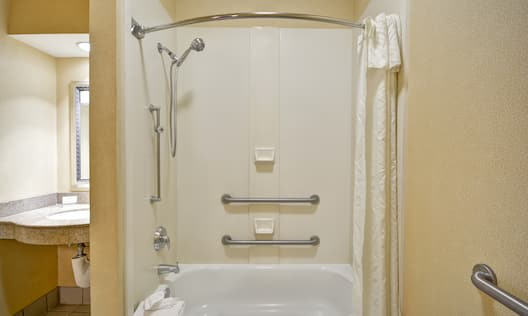 Accessible Bathtub With Grab Bars, Handheld Showerhead, Brightly Lit Vanity Mirror, and Sink,