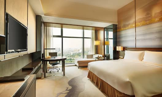 King Deluxe Room with bed, work desk, TV, lounge sofa, and outdoor garden view
