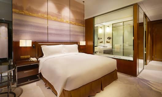 King Deluxe Room with bed and transparent window view of bathroom and shower