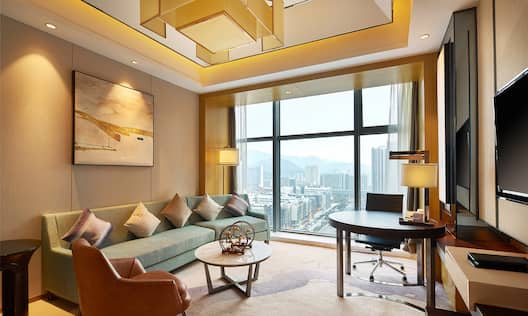 King Executive Suite living area with lounge sofa and chair, work desk, TV, and floor-to-ceiling windows with outdoor view
