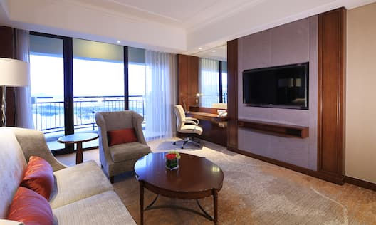 Sofa, Coffee Table, Armchair, Floor Lamp, Balcony With Open Drapes, Wall Mirror Above Work Desk, and TV in Deluxe Suite