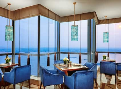 Place Settings and Flowers on Tables With Plush Blue Armchairs by Windows With Sunset View in Executive Lounge