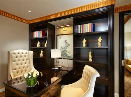 Two Arm Chairs at Desk in Presidential Suite With Bookshelves, Wall Art,  Illuminated Lamp, and Open Doorway to Living Area
