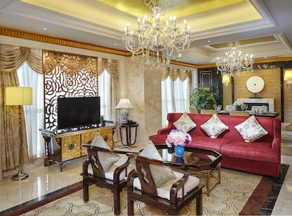 Two Arm Chairs, Coffee Table, Red Sofa, Floor Lamp, TV, Windows with Sheer Drapes and Seating for Six at Dining Table in Presidential Suite