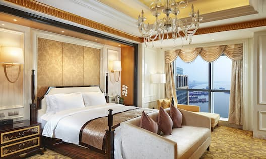 King Bed Between Two Illuminated Lamps Above Bedside Tables, Bed Bench, Chandelier, Floor Lamp, Chaise Lounger, and Window With Open Drapes to Expansive River View in Presidential Suite
