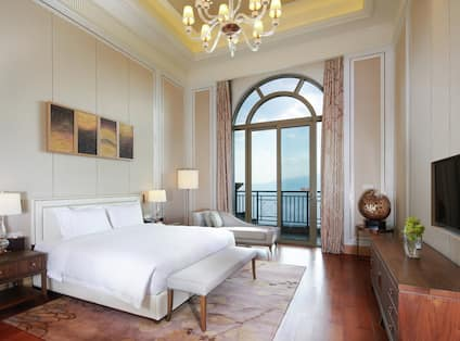 Spacious executive bedroom with king bed, large glass door onto balcony, dresser, TV set into wall