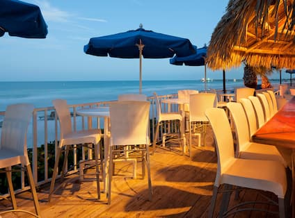 Tiki Bar with Bar Chairs, Tables, Umbrellas, and Ocean View