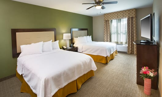 Suite Bedroom With Two Queen Beds, Bedside Table, Lamp, Ceiling Fan, Window and TV