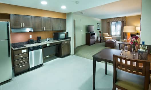 Suite Kitchen With Wall Art, Fridge, Wood Cabinets, Microwave Over Stovetop, Sink, Dishwasher, Coffee Maker, and Dining Table With Seating for Two