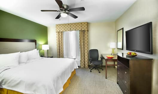 King Bed and Bedside Table With Lamp, Ceiling Fan, Work Desk by Window, and TV in Suite Guest Room