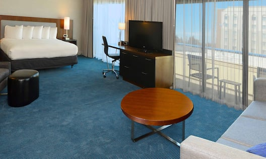 King Bed, Illuminated Lamp on Bedside Table, Windows With Sheer Drapes, Work Desk, TV, Balcony, Coffee Table, and Sofa in Non-Smoking Junior Suite