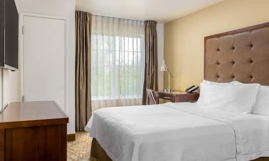 Queen Suite Separate Bedroom with One Queen Bed, Wall-mounted HDTV, Dresser and Large Window
