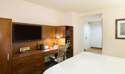 Wall Art, Queen Bed, TV, Illuminated Lamp on Work Desk, Hospitality Center With Microwave, Keurig, and Mini Fridge and Entry Door
