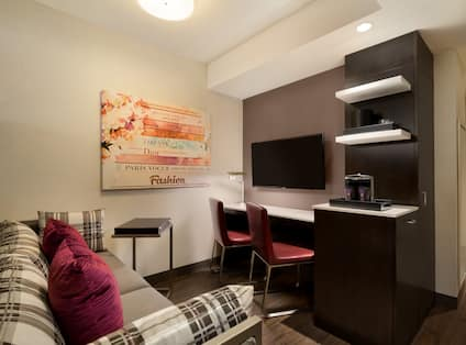 Guest Suite Lounge Area with Sofa, Work Desk, Wall Mounted HDTV and Coffee Machine