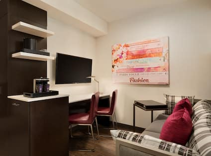 Guest Studio Lounge Area with Sofa, Work Desk, Wall Mounted HDTV and Coffee Machine