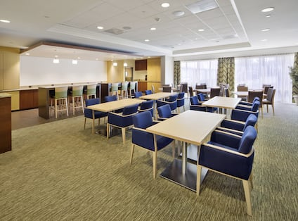 Tables With Blue Chairs Settings, Counter With Green Chairs, and Windows With Sheer Drapes in Solaris Café