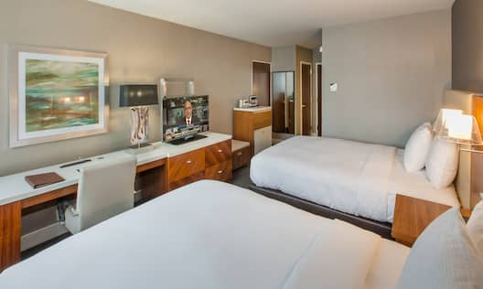 Two Queen Beds, Illuminated Lamp Above Bedside Tables, Wall Art Above Work Desk With Ergonomic Chair, HDTV, Hospitality Center, and Full Length Mirror in Guest Room