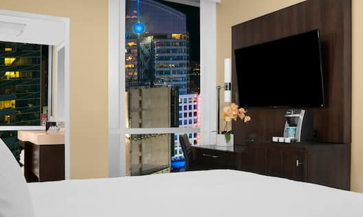 Guestroom with bed, TV and large windows