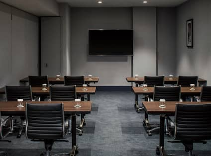 Classroom Setup in Meeting Room With Drinking Glasses on Tables, Chairs, TV and Wall Art