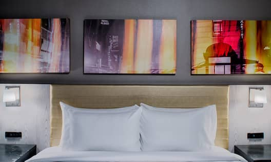 Wall Art Above King Bed, Illuminated Lamps, and Bedside Tables in Guest Room