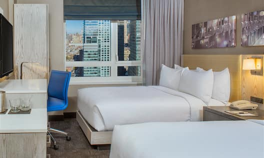 Wall Art Above Two Queen Beds, Illuminated Lamp, Bedside Table, Hospitality Center, TV, Work Desk With Blue Chair, and Window With Open Drapes to City View in Guest Room
