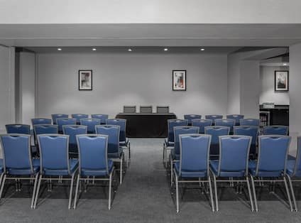 Meeting Room Arranged Theater Style With Rows of Blue Chairs Facing Wall Art ans Speaker's Table With Two Chairs and View of Refreshment Area