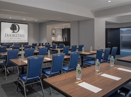 Classroom Setup in Meeting Room 1 With Entry, Refreshment Area, Tables and Chairs Facing Presentation Screen