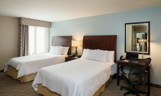 Double guestroom with beds and work desk