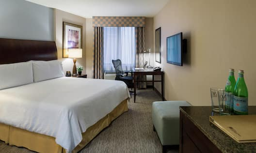 Guestroom with bed, work desk and TV