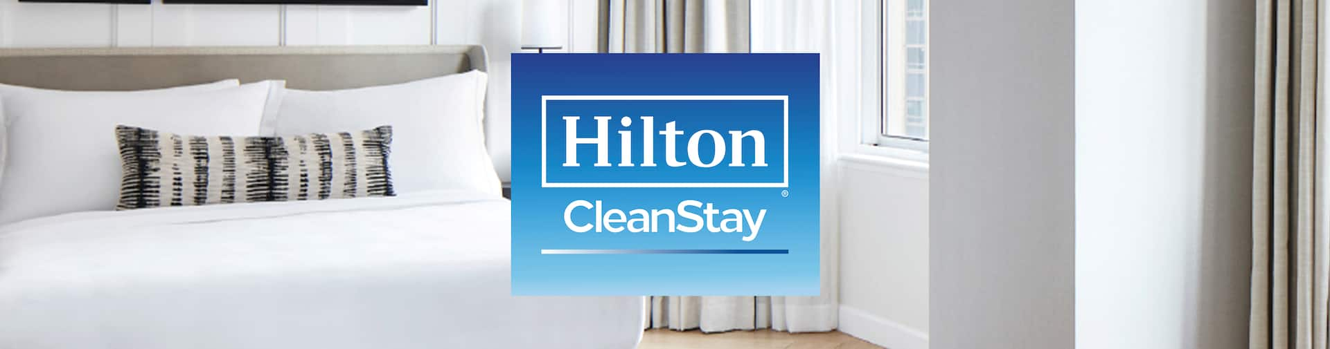Hilton CleanStay logo over an image of a hotel bedroom