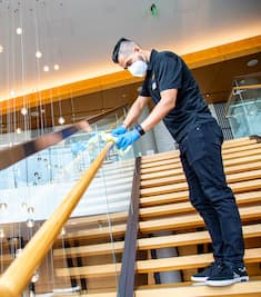A Hilton employee wearing rubber gloves and a face mask sanitizes a hotel staircase.