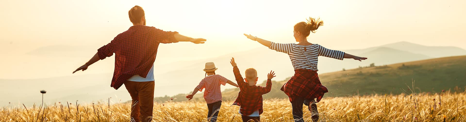 A family of four in a field running into the sunset