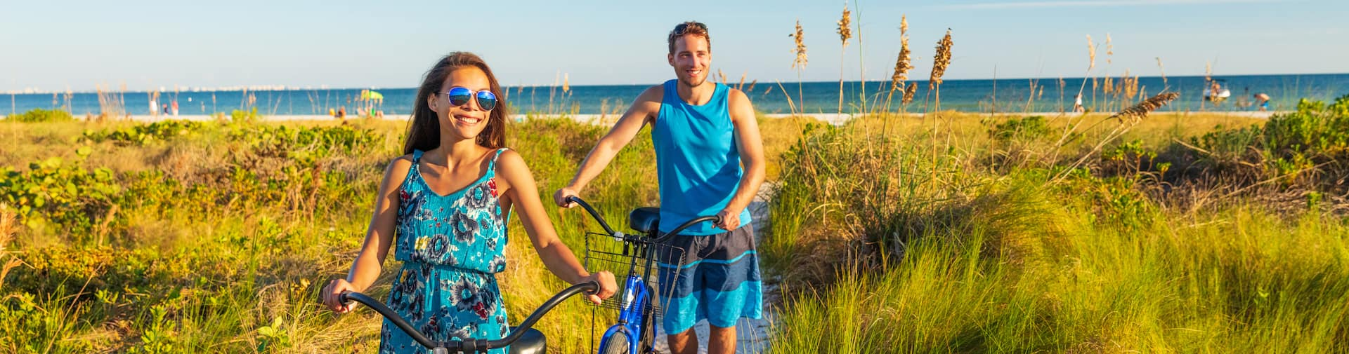 Happy couple biking on the beach.