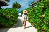 Woman walking on path to beach