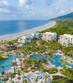 Aerial view of the pools and grounds at Conrad Punta de Mita with the ocean in the background.