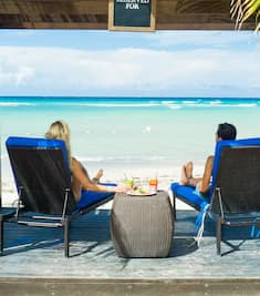 A couple sit under a cabana and look out to the ocean