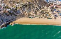 a bird's eye view of a hotel resort built into a cliff on a beach
