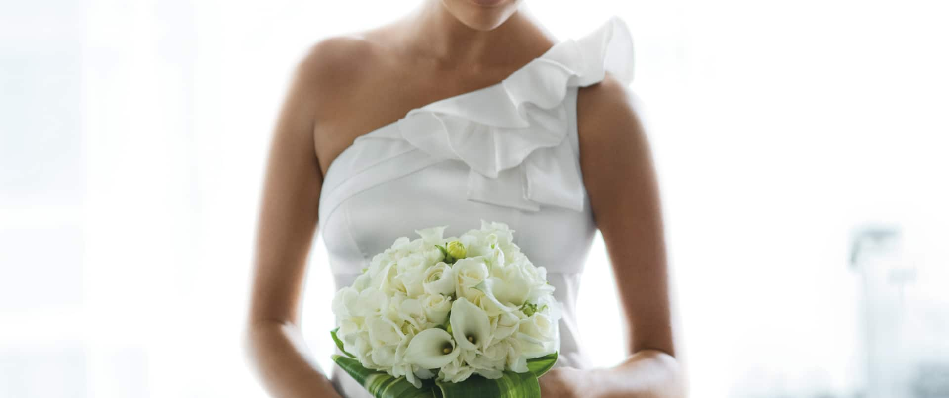 Brunette Bride With Closed Eyes Holding Bouquet of White Flowers Standing by Large Window
