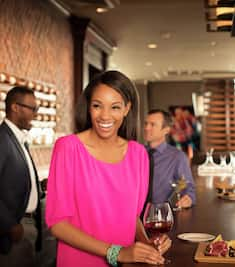 A smiling woman in pink stands at a bar with a glass of wine