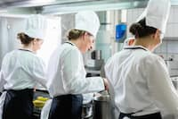 Group of team members cooking in industrial kitchen