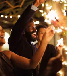 People Smiling and Holding Up Sparklers at Evening Event