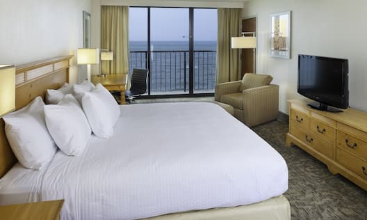 King Bed, Work Desk, Open Drapes to Balcony View, Illuminated Floor Lamp, Armchairs, and TV in Guest Room