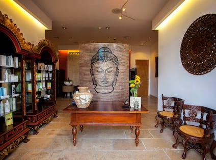 Products on Shelves, Buddha Art Feature, Table, Chairs and Wall Art in Spa Lobby