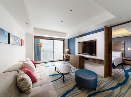 Suite Living Room with Lounge Seating, Work Desk, Television, Entry to Bedroom, Ocean View and Balcony