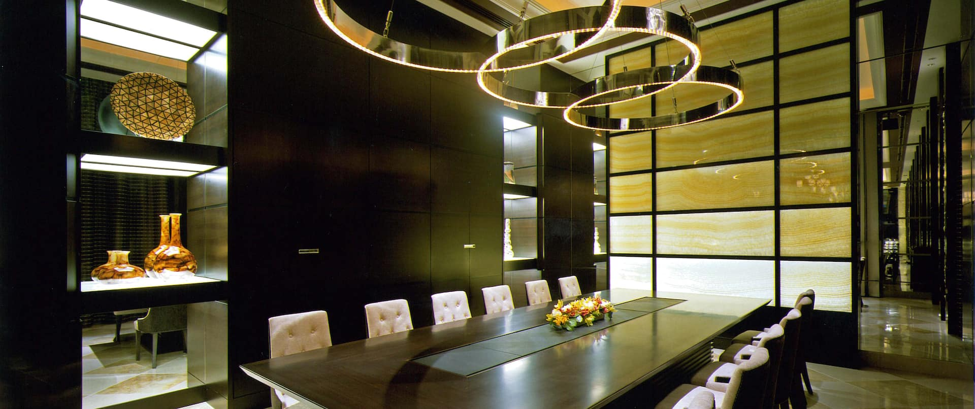 View of Meeting Room Interior With Mirrored Cabinet, Decorative Lighting, and Seating for 12 at Boardroom Table