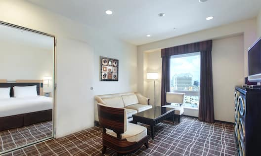 Doorway Open to King Bed, Suite Living Area With Wall Art Above Sofa, Two Chairs, Coffee Table, Floor Lamp, Window With Open Drapes, and TV